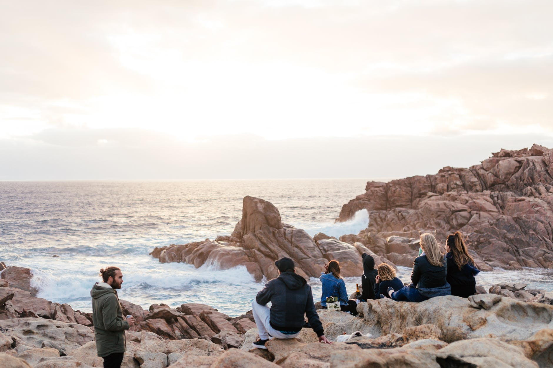 group of friends resting on rocky coast