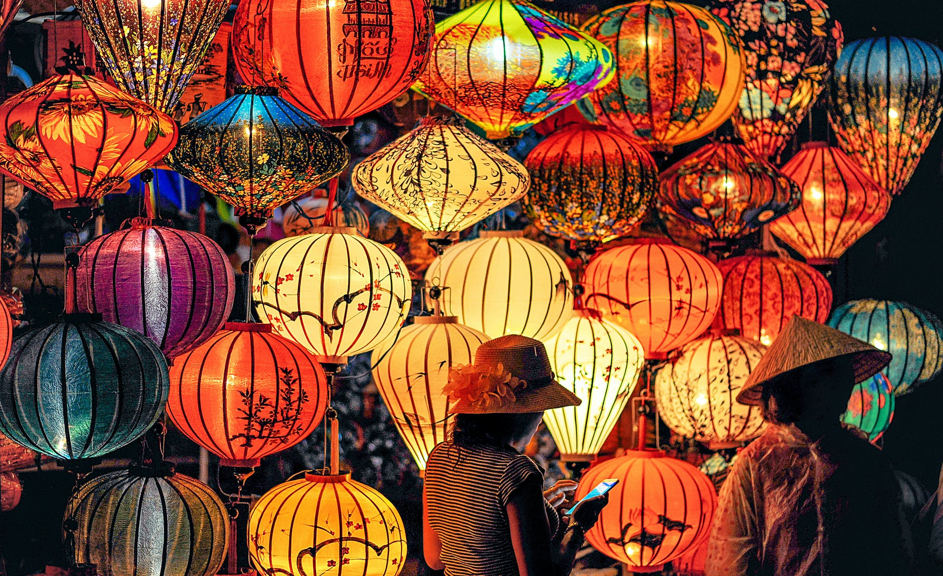 two person standing near assorted color paper lanterns